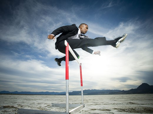 Stock Photo: 1660R-26776 Low angle view of a businessman jumping over a hurdle in a race