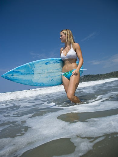 Stock Photo: 1660R-26934 Portrait of a young woman holding a surfboard