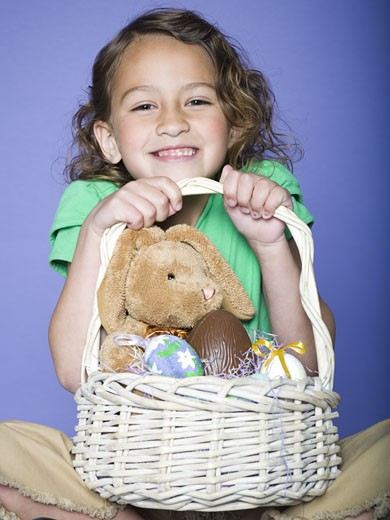 Portrait of a girl holding Easter eggs in a wicker basket : Stock Photo