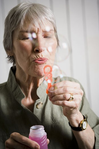 Portrait of an elderly woman blowing bubbles with a bubble wand : Stock Photo