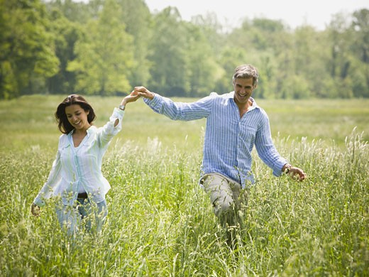 man and a woman holding hands and running in a field : Stock Photo