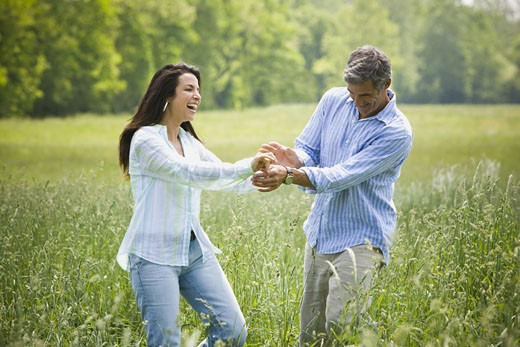 Stock Photo: 1660R-27208 man and a woman holding hands in a field