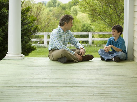 Stock Photo: 1660R-27283 Profile of a man and his son sitting on a wooden floor
