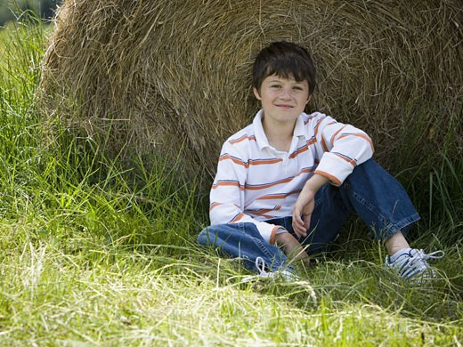 Stock Photo: 1660R-27295 Portrait of a boy sitting against a hay bale