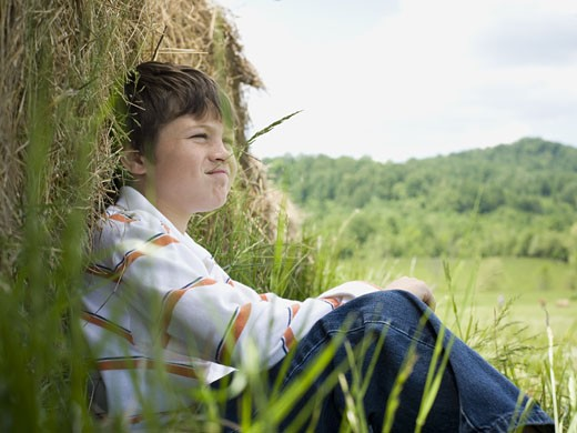 Portrait of a boy sitting against a hay bale : Stock Photo