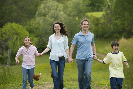 woman and a man with their son and daughter running in a field : Stock Photo