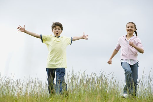 Stock Photo: 1660R-27325 Boy and a girl running in a field