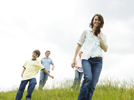 Low angle view of a woman and a man with their son and daughter in a field : Stock Photo
