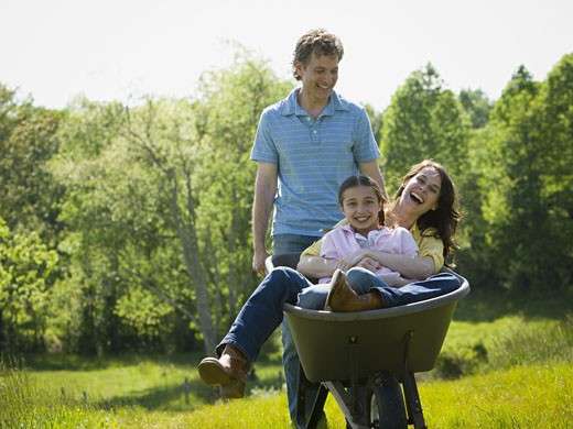 Stock Photo: 1660R-27362 man pushing his daughter and his wife in a wheelbarrow