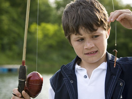 Close-up of a boy holding a fishing rod : Stock Photo