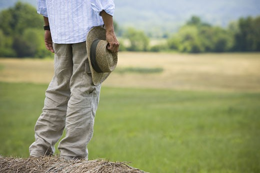 Low section view of a man standing on a hay bale : Stock Photo