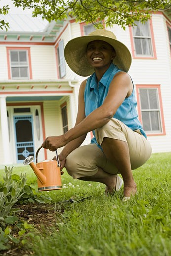 Stock Photo: 1660R-27506 Senior woman watering plants