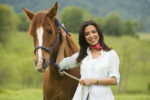 Portrait of a woman holding the reins of a horse : Stock Photo
