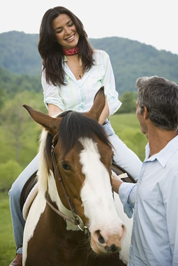 Stock Photo: 1660R-27574 woman sitting on a horse with a man beside her