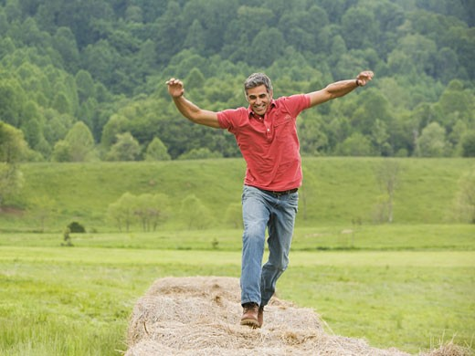 Portrait of a man jumping on a hay bale : Stock Photo
