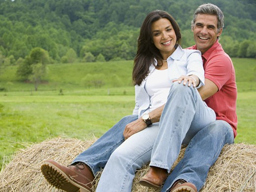 Stock Photo: 1660R-27615 man and a woman sitting on a hay bale