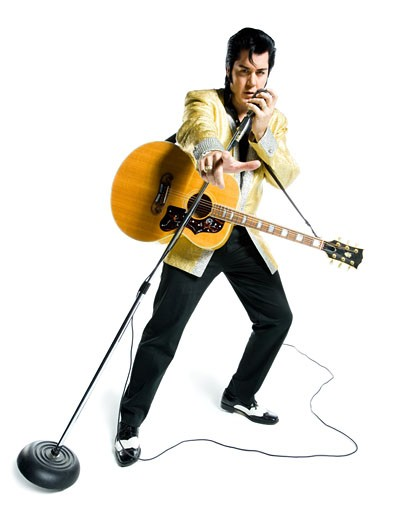 Stock Photo: 1660R-27664 Portrait of an Elvis impersonator singing into a microphone