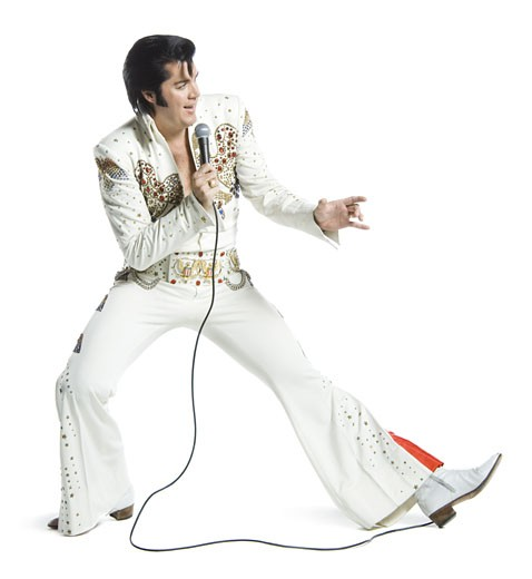 An Elvis impersonator singing into a microphone and jumping : Stock Photo