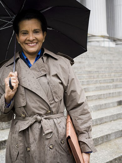 Low angle view of a woman holding an umbrella and smiling : Stock Photo