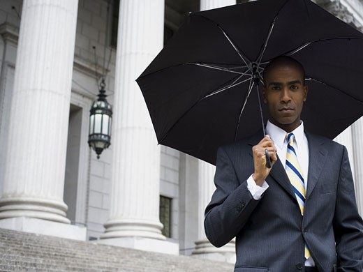 Portrait of a male lawyer standing in front of a courthouse and holding an umbrella : Stock Photo