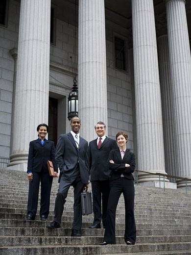 Stock Photo: 1660R-27855 Low angle view of lawyers standing on the steps of a courthouse