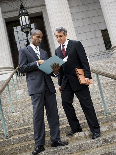 Stock Photo: 1660R-27862 Low angle view of two men looking at documents on the steps of a courthouse