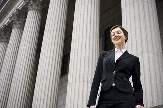 Low angle view of a female lawyer standing in front of a courthouse : Stock Photo