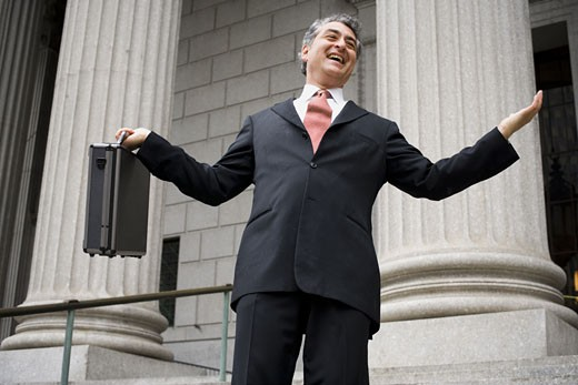 Stock Photo: 1660R-27883 Low angle view of a male lawyer holding a briefcase and laughing