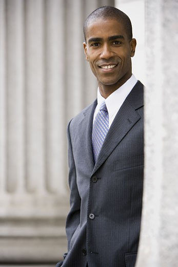 Portrait of a male lawyer standing in front of a courthouse and smiling : Stock Photo