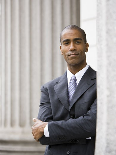 Portrait of a male lawyer standing with his arms folded : Stock Photo