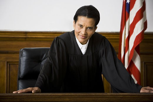 Portrait of a female judge leaning against a bench : Stock Photo