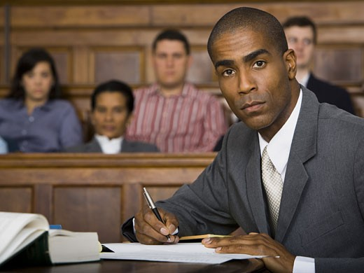 Portrait of a male lawyer sitting in a courtroom : Stock Photo