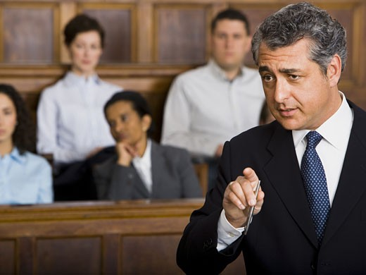 A male lawyer talking in a courtroom : Stock Photo