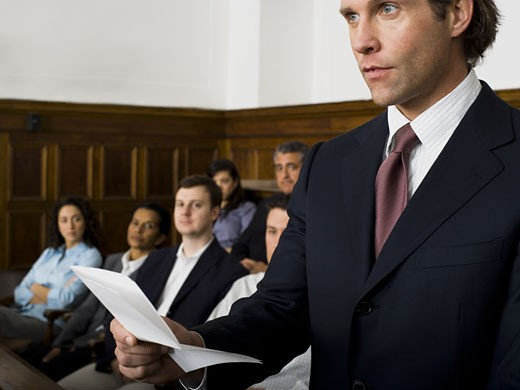 Stock Photo: 1660R-27945 Juror standing in a jury box and reading the verdict
