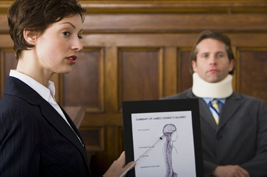 Stock Photo: 1660R-27954 A female lawyer pointing at evidence in front of a victim in a courtroom