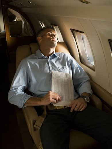 A businessman sleeping in an airplane : Stock Photo