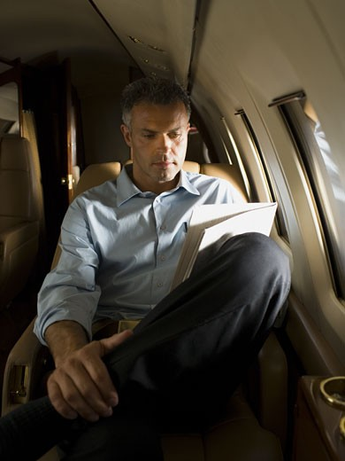 Stock Photo: 1660R-27998 A businessman reading a newspaper in an airplane