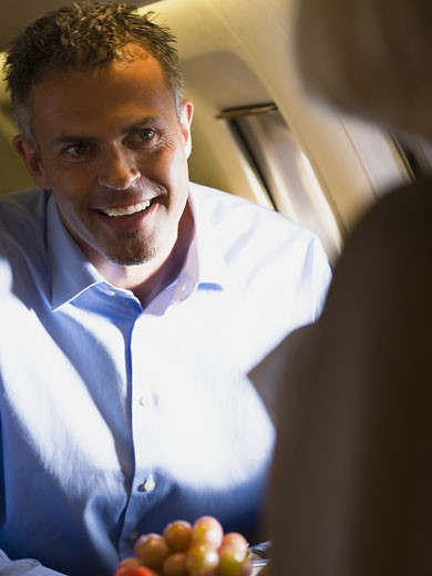 Stock Photo: 1660R-28013 A businessman smiling in an airplane
