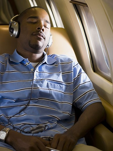Stock Photo: 1660R-28027 A man listening to music on headphones in an airplane