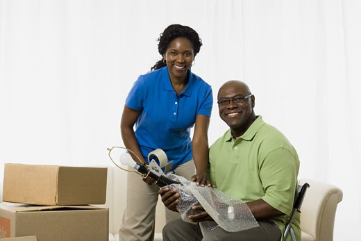 Stock Photo: 1660R-28051 Portrait of a senior couple smiling and packing up a lamp