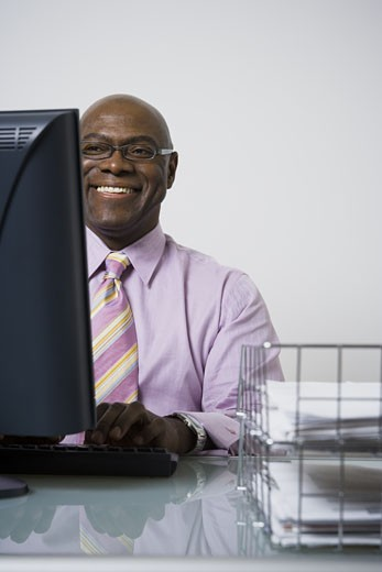 Close-up of a businessman using a computer and smiling : Stock Photo