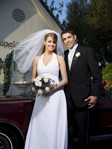 Portrait of a newlywed couple standing near a car in front of a chapel : Stock Photo