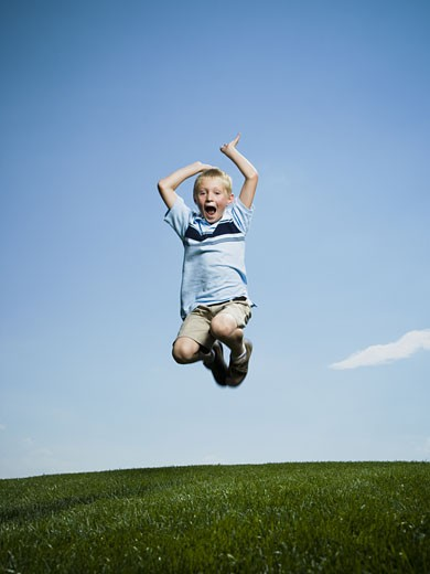 Portrait of a boy jumping with his arms raised : Stock Photo