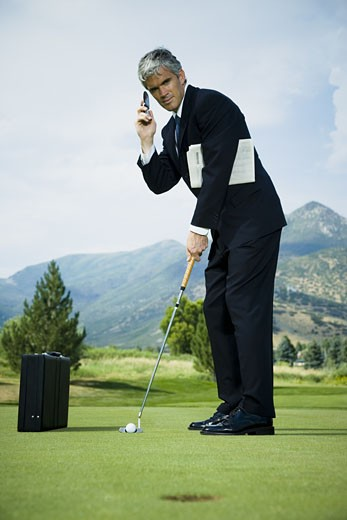 Stock Photo: 1660R-28119 Profile of a businessman playing golf and talking on a mobile phone