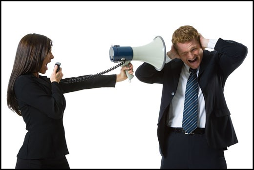 Stock Photo: 1660R-28168 Profile of a teenage girl shouting in a megaphone with a businessman covering his ears