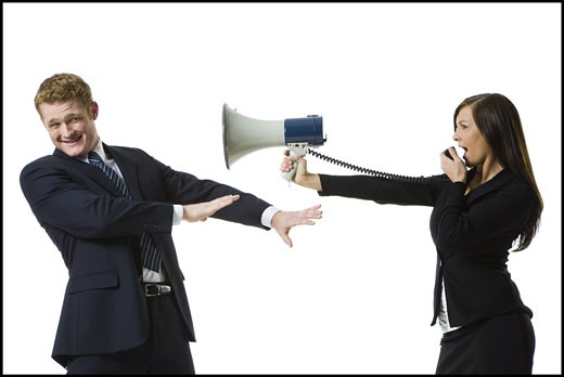 Stock Photo: 1660R-28169 Profile of a teenage girl shouting in a megaphone with a businessman covering his ears