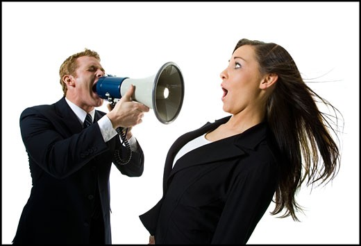 Close-up of a businessman shouting at a teenage girl through a megaphone : Stock Photo