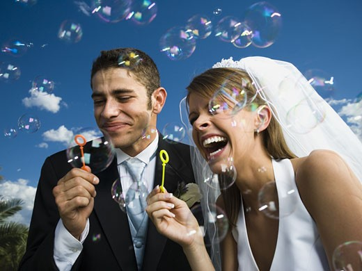 Stock Photo: 1660R-28190 Close-up of newlywed couple blowing bubbles with a bubble wand
