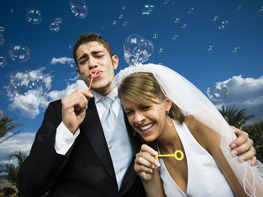 Close-up of newlywed couple blowing bubbles with a bubble wand : Stock Photo
