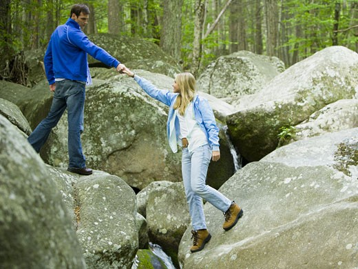 Stock Photo: 1660R-28286 Young man helping a young woman climb a rock